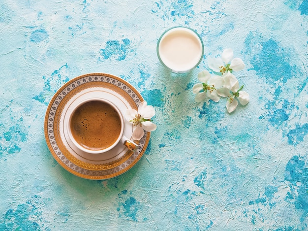 Coffee and a glass of milk on a blue background. ramadan food.
