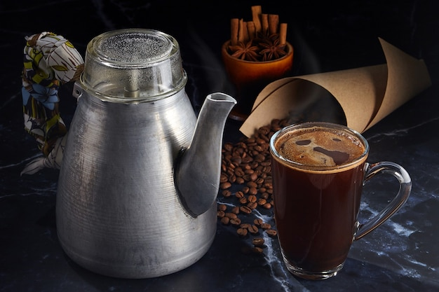 Coffee in a glass mug and a vintage aluminum geyser coffee maker