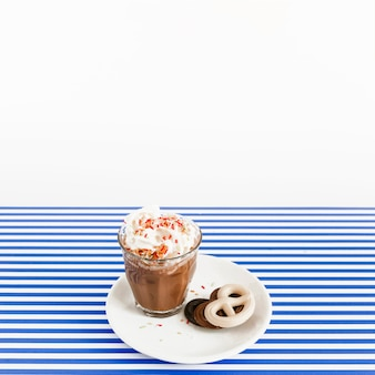 Coffee glass with whipped cream and pretzel chocolates on plate over white and blue stripes backdrop