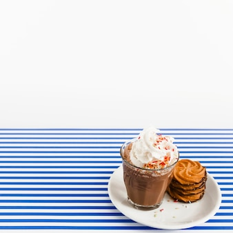 Coffee glass with whipped cream and stack of cookies on plate over backdrop
