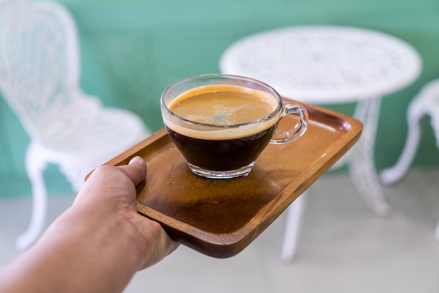 Coffee in glass on the wooden plate in the hands of the waitresses in coffee shop.