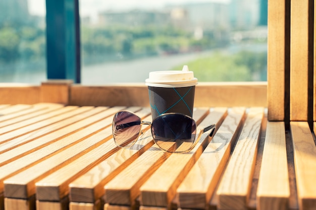Coffee to go and sunglasses on a wooden table with a beautiful view of the river in the big city