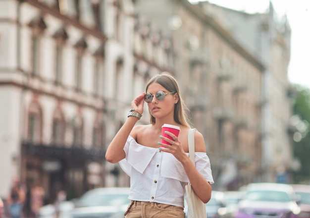 Coffee on the go. young fashion woman in trendy summer clothes holding coffee cup while walking around the city