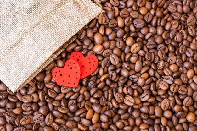 コーヒーの穀物と木製のテーブルに赤いハート。コーヒーは好きな飲み物です