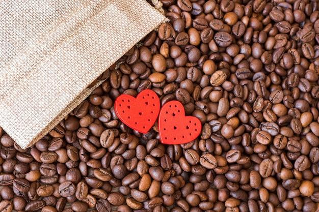 コーヒーの穀物と木製のテーブルに赤いハート。