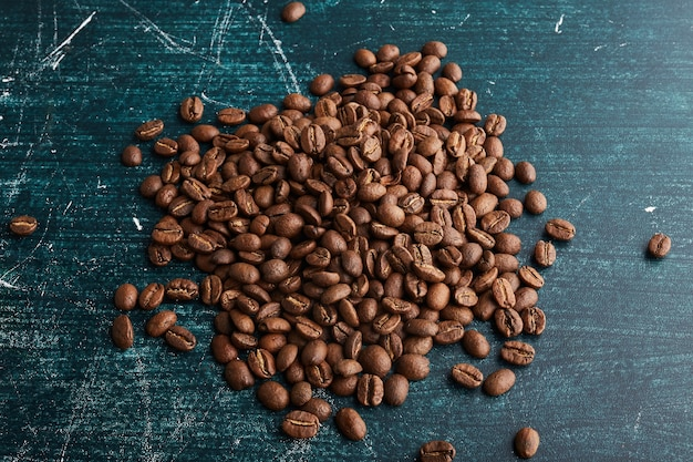 Coffee grains on blue surface.