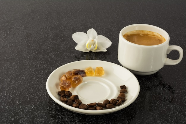 Coffee grains, cup of coffee and orchid