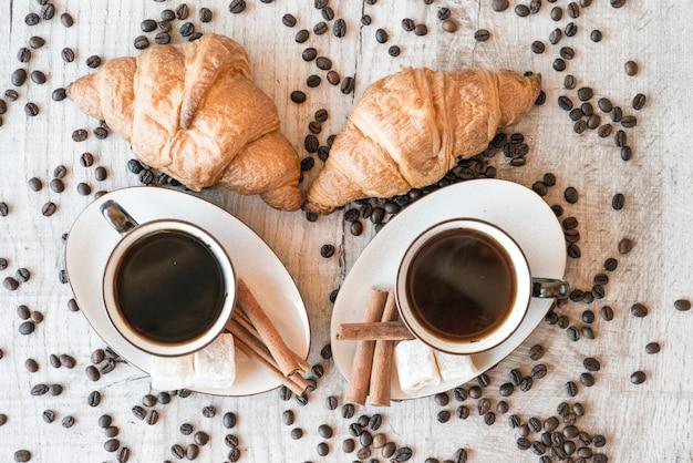 お菓子とクロワッサンと木のテーブルの上のコーヒーの穀物