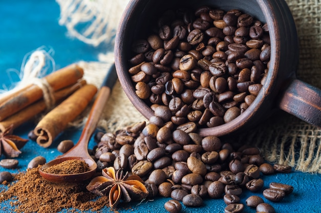 Coffee grains pouring out of a clay cup  and scattered on a blue texture