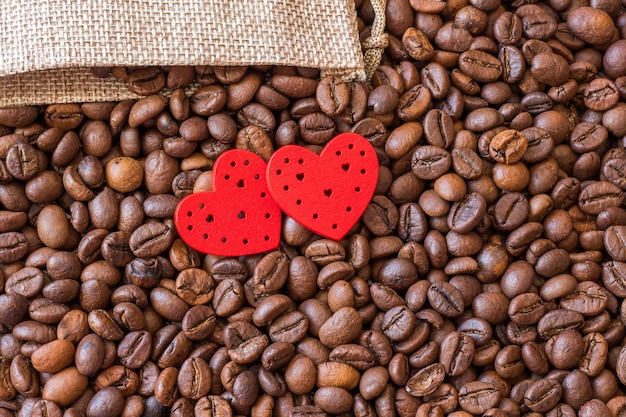 Coffee grains and red hearts on a wooden table. coffee is a favorite drink_
