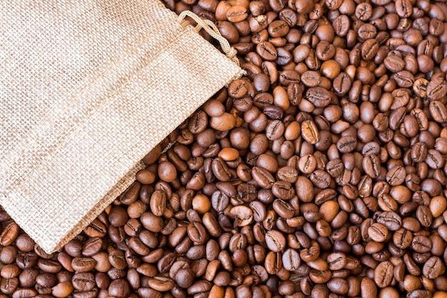 コーヒーの粒がバッグから飛び散ります。コーヒー豆の背景_