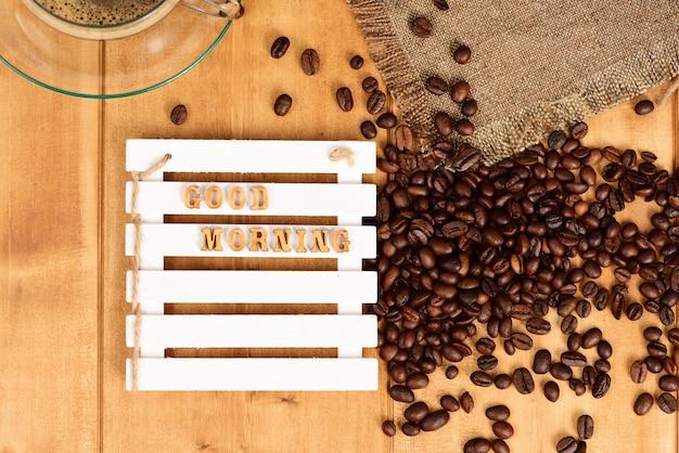 Зерна кофе разбросаны на деревянном столе с надписью доброе утро