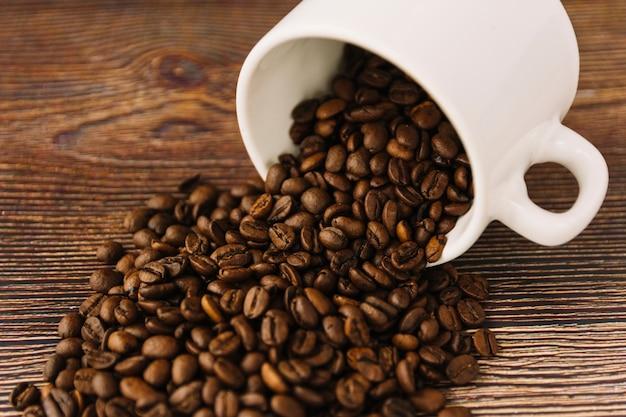 Chicchi di caffè che si spargono dalla tazza