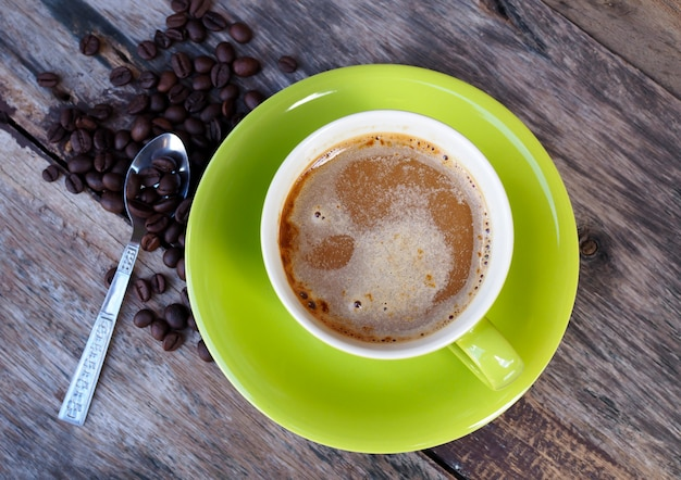Coffee in green cup on old wooden table background, top view