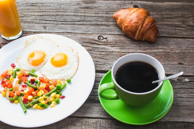 Coffee in a green mug on wooden surface with food, delicious breakfast