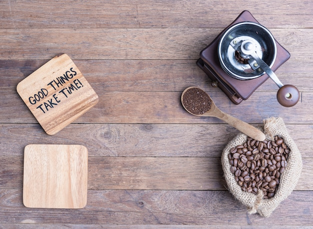 Coffee grinder, coffee beens in burlap and blank wood plate on wooden table, flat lay with copy space