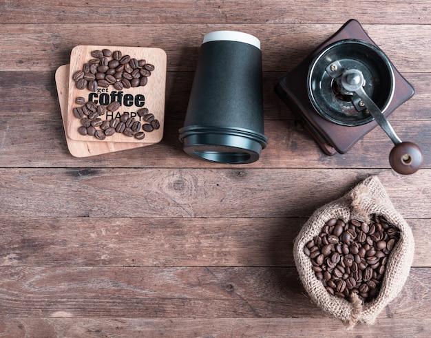 コーヒーグラインダー、黄麻布のコーヒーbensと木製のテーブルに黒い紙cpフラット横たわっていた