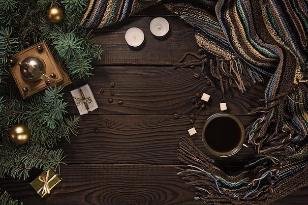 木製のテーブルの上のコーヒーグラインダー、カップ、キャンドル、クリスマスツリー。上面図