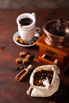 Coffee grinder, cup of coffee and coffee beans bag in background.