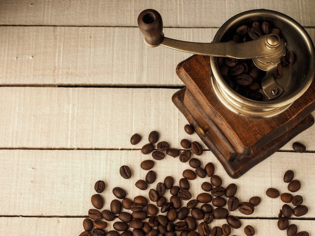 Coffee grinder mill with coffee grains on a light wooden background.