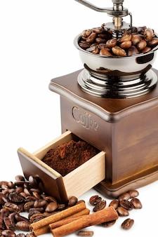 Кофемолка с кофейными зернами и корицей