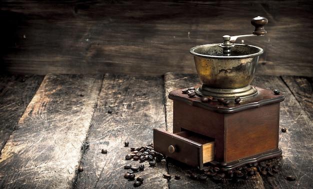 木製の背景にコーヒー豆とコーヒーグラインダー