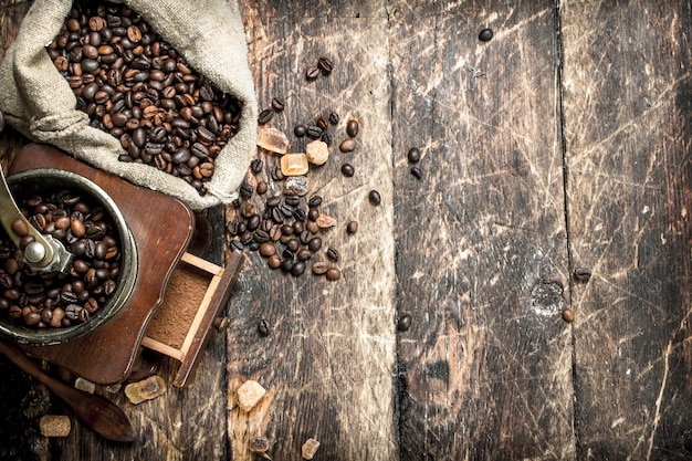 Coffee grinder with coffee beans. on a wooden background.
