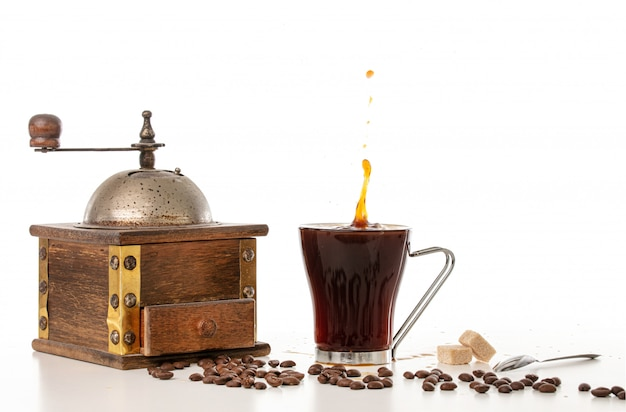 Coffee grinder with a cup of coffee and splashes