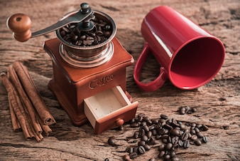 Coffee grinder with red cup on wooden table