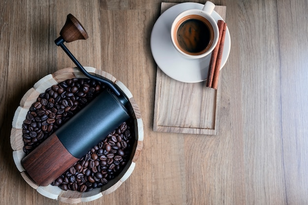 Coffee grinder in wooden bucket with coffee beans and cup of espresso on wooden table