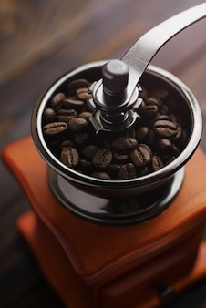 Coffee grinder on a wooden table in a rustic style. roasted coffee beans in a coffee grinder. preparing coffee for brewing.