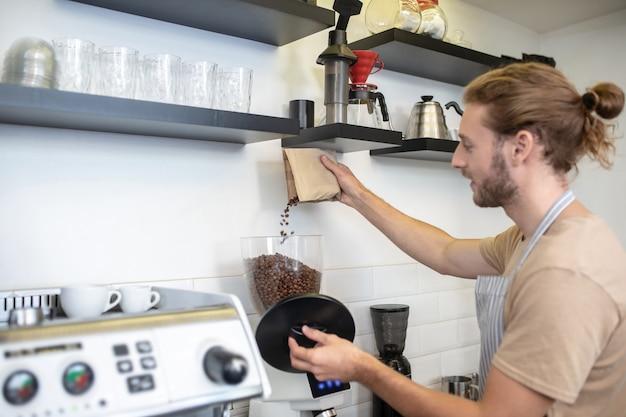커피 그라인더. 프로필에 젊은 성인 남자가 카페에 서 커피 분쇄기에 커피 콩을 붓는