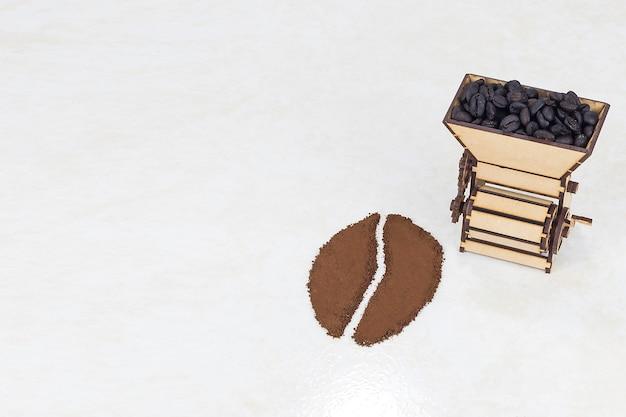 白で分離されたコーヒーから作られたコーヒー豆とコーヒー粉砕機のコンセプト