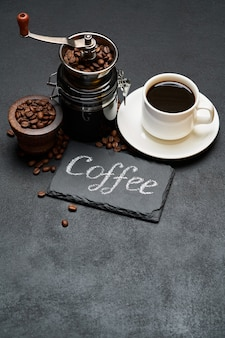 Coffee handwritten inscription sign on chalk board and cup of espresso coffee