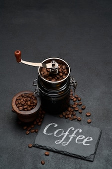 Coffee handwritten inscription sign on chalk board and hand grinder on dark concrete table
