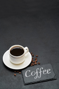 Знак кофе рукописной надписи на доске и чашка кофе эспрессо