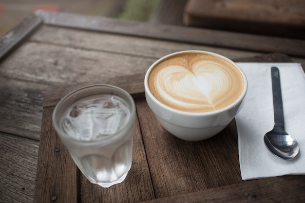 Coffee heart latte art with water on wooden table in holiday