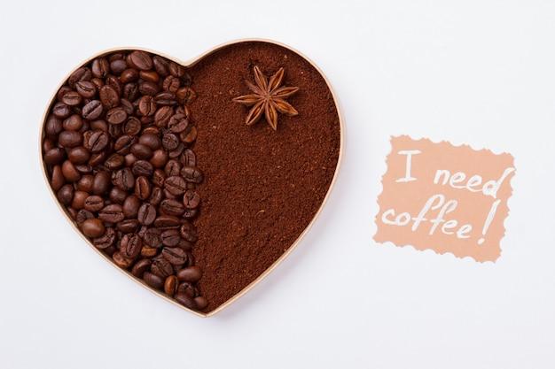 Кофейное сердце из зерен и порошка растворимого кофе. изолированные на белой стене мне нужен кофе.