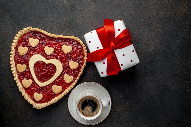 Coffee, heart-shaped cake and a gift with a red ribbon for valentine's day