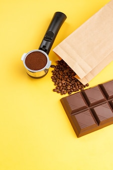 Coffee in a holder, coffee beans, bar of chocolate against yellow background