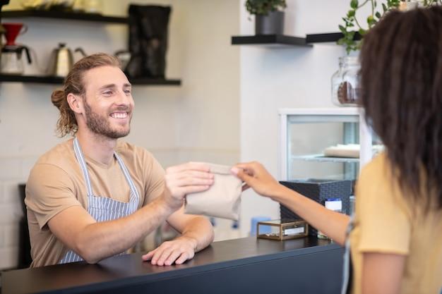 喫茶店。コーヒーショップのカウンターの後ろのエプロンで若いひげを生やした男性が女性に小さな紙袋を与える笑顔