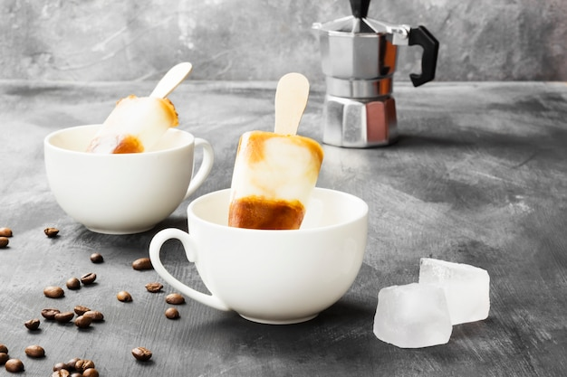 Coffee ice cream popsicles in white cups