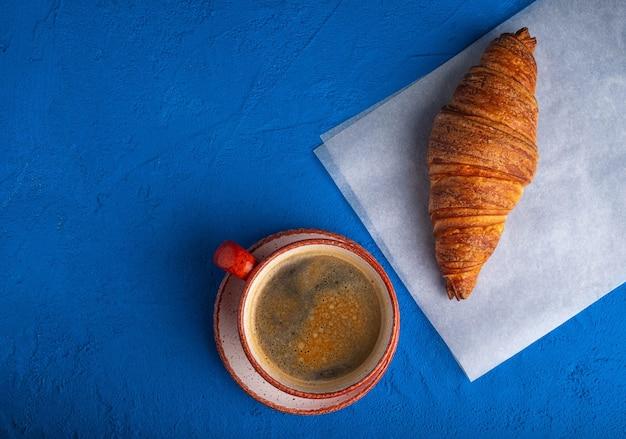 Кофе в чашке и круассан на синем столе