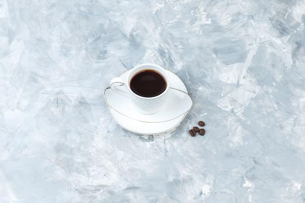 青い大理石の背景の上のカップのコーヒー。ハイアングルビュー。