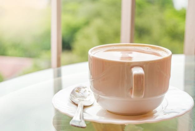 Кофе в чашке на стеклянном столике, балкон с видом на природу и море, вкусный завтрак на рассвете.