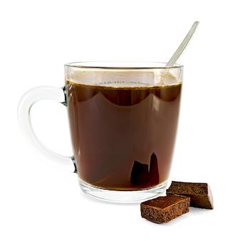 Кофе в стеклянной чашке, ложка, два ломтика темного пористого шоколада, изолированные на белом фоне