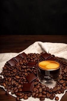 Кофе в стеклянной чашке на деревянном столе. кофейные зерна и кусочки шоколада.