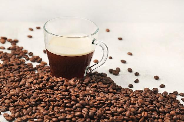 コーヒー豆の背景にガラスカップのコーヒー