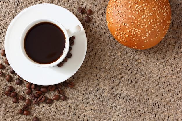 マグカップとソーサーにコーヒー、黄麻布のテーブルクロスにゴマとコーヒー豆のパン。上面図。