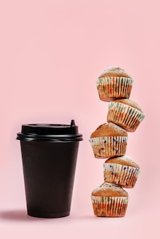 紙コップとピンクの背景に新鮮なマフィンのコーヒー